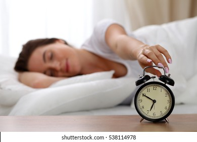 Sleepy young woman stretching hand to ringing alarm willing turn it off. Early wake up, not getting enough sleep, getting work concept.