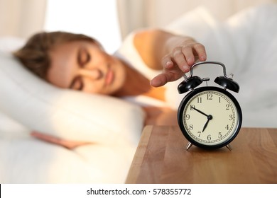 Sleepy young woman stretching hand to ringing alarm to turn it off. Early wake up, not getting enough sleep, getting work concept.