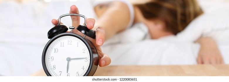 Sleepy young woman trying kill alarm clock while bury face in pillow. Early wake up not getting enough sleep getting work concept. Female stretching hand to ringing alarm willing turn it off