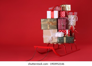 Sleigh with gift boxes on red background. Space for text