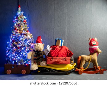Sleigh of Santa Claus, bag with gifts, Christmas tree, Christmas toys and luminous garlands. Rocking horse depicting a deer