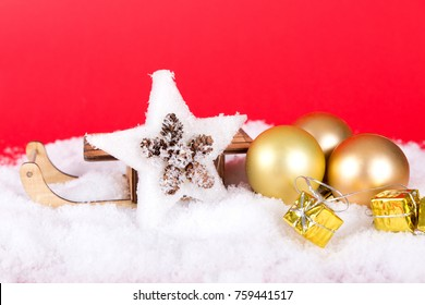 sleigh with a star, gifts and baubles on white snow and red background