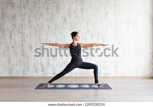 Schlankes asiatisches Mädchen, das in Yoga asana auf Matte auf Betonmauer steht. Ruhiges fokussiertes Mädchen, das in Warrior Two-Bewegung steht, Virabhadrasana-Pose, mit schwarzer Sportbekleidung. Kein Stresskonzept.