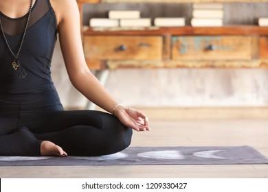 Slender asian yoga girl wearing black sportswear sitting in Lotus pose close up. Peaceful girl sitting in ardha Padmasana. Practicing yoga at home on mat. No stress, freedom, meditating concept.