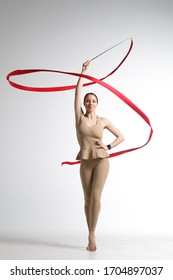 Slender athletic girl in beige sportswear dancing with a red gymnastic ribbon isolated on white background.