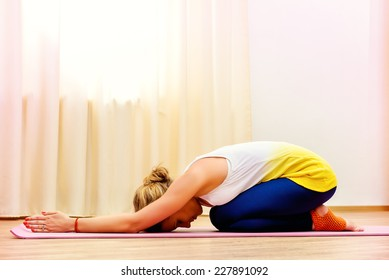 Slender athletic girl doing yoga exercises indoor. Professional trainer.