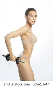 Slender athletic girl with a dumbbell in hand on the white background