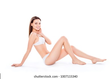 Slender, attractive, slim, charming, pretty woman sitting over white background in bra and bikini, looking at camera, demonstrating her perfect body, plain skin, wellness, wellbeing concept