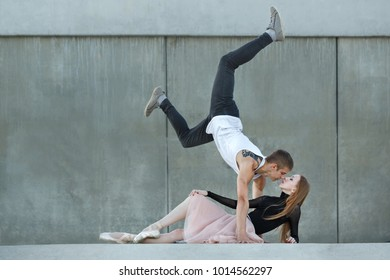 Slender ballerina dances with a modern dancer. Dating lovers. Passion and romance of dance. They look into each other's eyes. Performance on the streets.