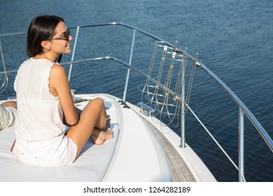 Slender and beautiful model wearing in white clothes sitting on boat bow. Beautiful brunette smiling and looking away at sea. Girl admiring view of sea and blue water while yachting.