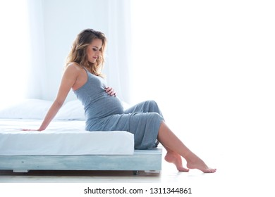 Slender beautiful pregnant young woman sitting on a bed near the window. Flowing bright daylight sunlight.