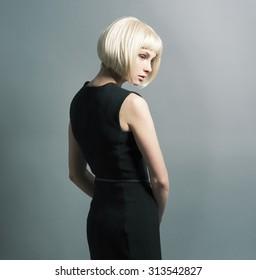 The slender blond with short hair standing sideways in black dress