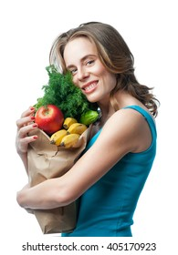 slender blonde holding a bag with vegetables and herbs