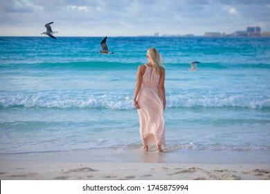 Slender blonde woman admires the sunrise at a Carribean sea.
