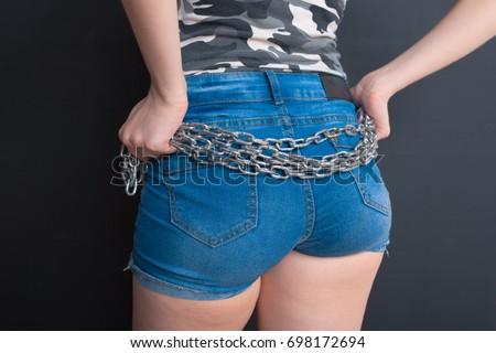 slender brunette girl in short denim shorts. holds the iron chain. short  hair and bee921d048