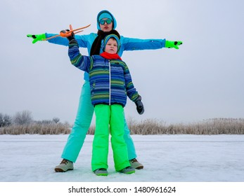 Slender cheerful mother in blue ski suit plays with children on snowy river. Boys with mom launch bright toy planes. Christmas Eve. Winter holidays in village. Family holidays.