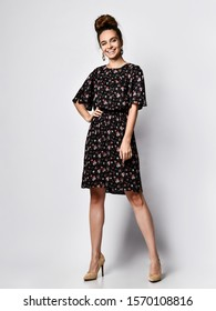 Slender curly female model in a silk dark dress with a red floral print, looking at the camera at full height. Cute girl in romantic clothes goes on a date, smiling pretty on a white background.
