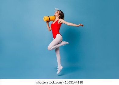 Slender dark-haired lady in red leotard and white pantyhose is holding yoga mat. Shot of woman in sports outfit of 80s on blue background