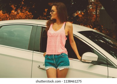 slender fashionable brunette in a pink t-shirt and shorts standing near the car and looks away in the autumn time