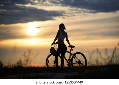 Slender female cyclist standing near bicycle and looking at sun and marvelous landscapes. Silhouette of sporty woman posing on trail in grass. Concept of motivation and healthy lifestyle.