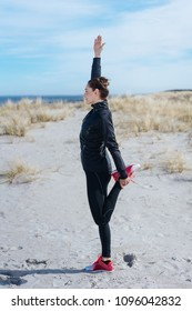 Slender fit woman working out on a beach standing balancing on one leg in a yoga position in a side view looking out towards the ocean