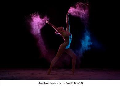 Slender girl dancing in color powder cloud