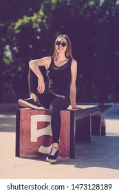 a slender girl dressed in black clothes and in black sunglasses sits on a box in a skatepark. summer sunny day