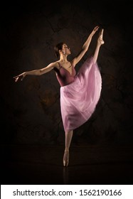 A slender girl in a pink skirt and beige top dancing ballet. Studio shooting on a dark background, isolated images.