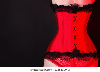 Slender girl in red waist pulling corset on black background. Sexual bdsm lingerie. Lady in narrow laced corset. Red lighting. Outfit for playing bdsm games. Sensual seductive underwear. Slim waist