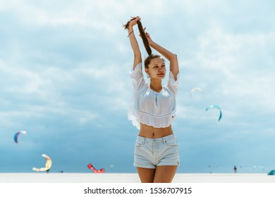 a slender girl in shorts and a blouse against the background of the sea, sky and flying kitesurfers