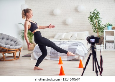 slender girl in sportswear at home engaged in Pilates. exercise for balance with a load on the hips. exercise trainer shows, writes a blog on video camera. balancing tenet to the cone of the feet
