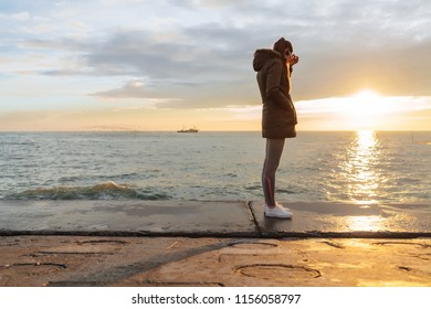 a slender girl in a warm jacket enjoys the sea view, listening to music on headphones