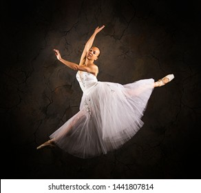 Slender girl in a white corset tutu dancing ballet. Studio shooting on a dark background, isolated images.