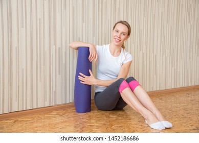 Slender girl in a white T-shirt holds a twisted gymnastic mat in her hands before training