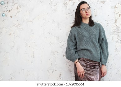 A slender gorgeous girl against a textured white wall.