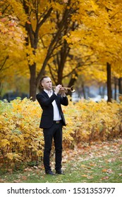 slender handsome trumpeter in black formal suit plays musical instrument golden trumpet in autumn park or forest eith many yellow leaves and trees