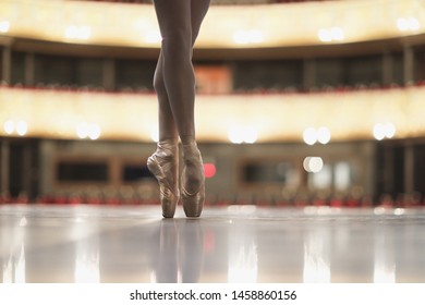 Slender legs of a ballerina in gold pointe on the stage of the theater
