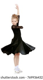 The slender little blonde girl dancer in the long dress of black color made specifically for performing .Girl stands sideways to the camera and raised his hand up.Isolated on white background.