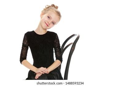 Slender little dancer posing near the old Vienna chair.