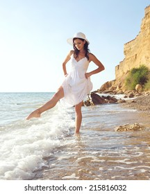 Slender romantic girl playing with waves on the beach. Summer vacation