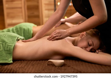 slender shirtless woman lying on chest receiving spa procedures massage on back, in spa center salon. beauty concept. side view