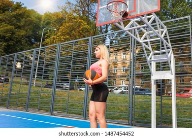 Slender sport girl with a basketbal wall in hand