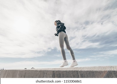 slender sports girl in gray leggings jogging in the open air