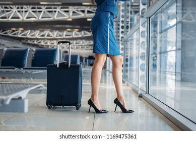 Slender stewardess and suitcase in airport hall