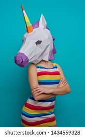 Slender, stylish model posing with paper 3D unicorn on head on blue background. Graceful girl in striped dress with slender waist, standing with crossed hands. Concept of papercraft.