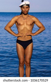 Slender, tanned, young guy, sailor. Standing in the sea water, put your hands on your hips