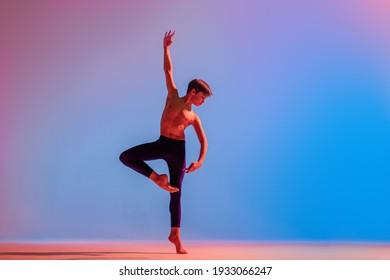 Slender teenage ballet boy dancer dances barefoot under a colored light.