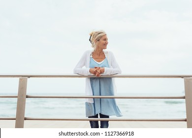 Slender trendy blond woman on a waterfront pier standing leaning on the rails looking to the side with a smile against an ocean backdrop