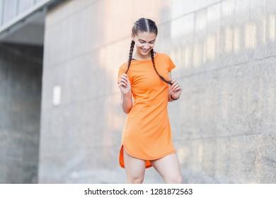 Slender white Caucasian girl in an orange sundress against the background of the wall. Happy girl on the street