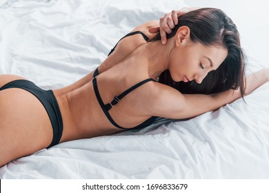 Slender woman in black underwear lying down on bed in room at daytime.
